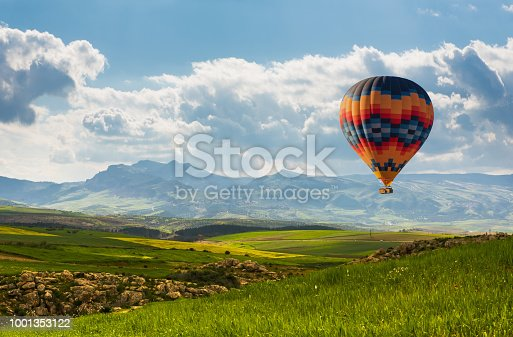 Colorful hot air balloon flying over green field and mountain