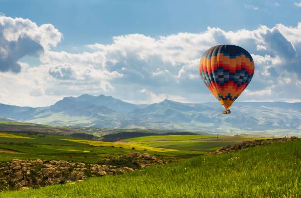 colorful montgolfière survolant champ vert - montgolfière photos et images de collection
