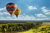 Colorful hot air balloon flying over green field and river