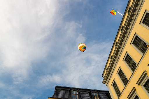 Stockholm, Sweden, May 29, 2018: Colorful color hot air balloon in blue sky white clouds over traditional typical sweden yellow buildings