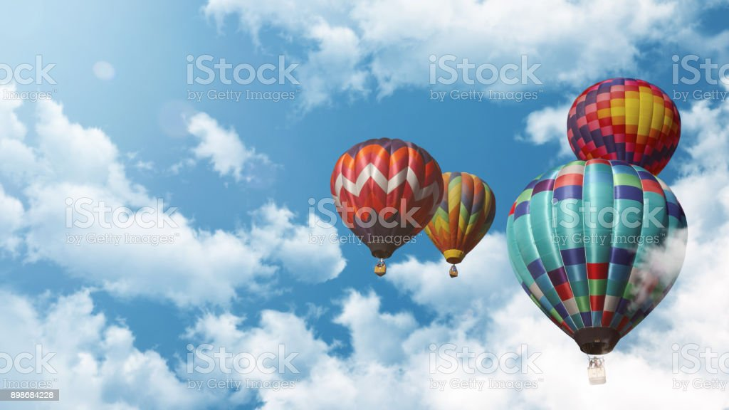Bunter Heißluftballon vor blauem Himmel mit Wolken und Sonne – Foto