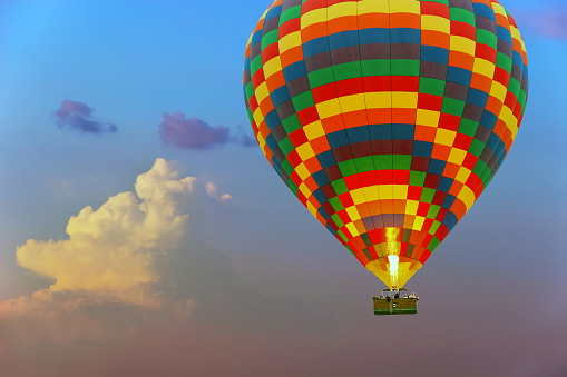 Colorful hot air balloon is flying at rose sundown sky of the cloud background