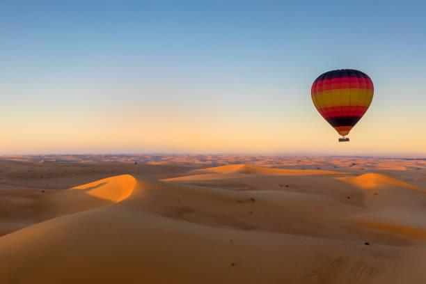 Bunte Heißluftballon über Wüste bei Sonnenaufgang – Foto
