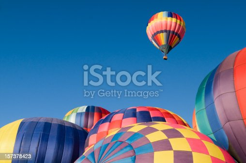 Hot air balloons on the ground create a colorful frame for the one that is rising above them.  A great metaphor for success or standing out from the crowd.