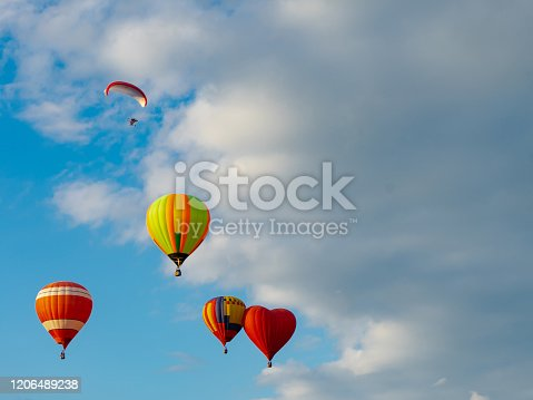 844061492 istock photo Colorful hot air balloons flying in blue sky. Few colorful, hot air balloons descending at the Balloon Festival. 1206489238