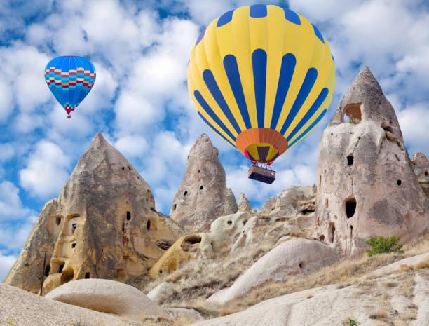 kleurrijke hete lucht ballonnen vliegen in cappadocië, turkije - aardpiramide stockfoto's en -beelden