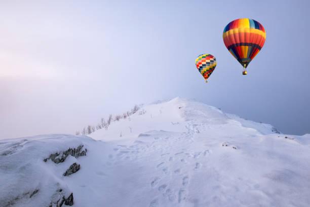 bunte heißluftballons fliegen auf schneehügel mit schneesturm - eis ballons stock-fotos und bilder