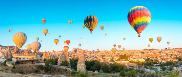 kleurrijke hete lucht ballonnen vliegen over op sprookjesachtige schoorstenen in nevsehir, göreme, cappadocië turkije. hete lucht ballonvlucht bij spectaculaire cappadocië turkije. - aardpiramide stockfoto's en -beelden