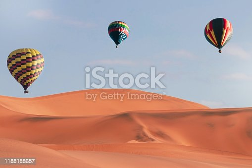 844061492 istock photo Colorful hot air balloons flying over sand dune seven, Walvis Bay, Namibia. 1188188657