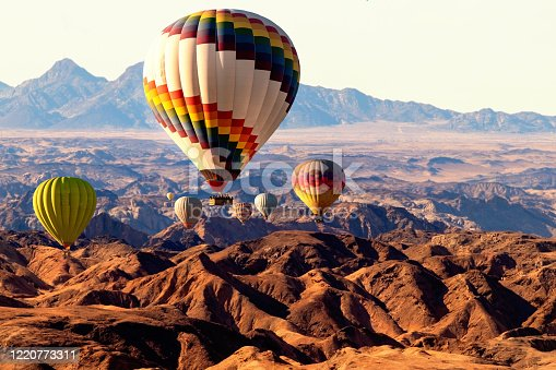530709531 istock photo Colorful hot air  balloons flying over the moon valley mountain. Africa. Namibia. 1220773311