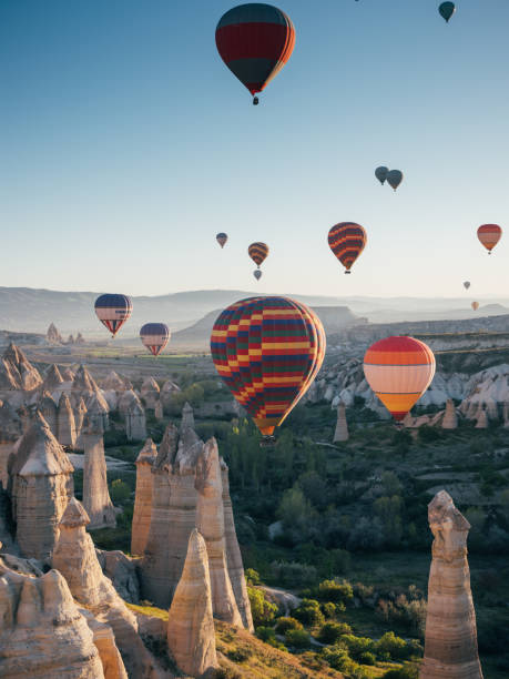 Colorful hot air balloons flying over the valley at Cappadocia Colorful hot air balloons flying early in the morning with Rocks and Fire over the valley at Cappadocia/Nevşehir transvaal province stock pictures, royalty-free photos & images