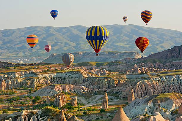 colorful hot air balloons flying over the valley at cappadocia, - aardpiramide stockfoto's en -beelden