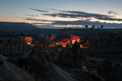 Hot air balloons glowing in early morning while inflating among rocks of mountain landscape in Cappadocia. Colorful illuminated balloons in blue hour of sunrise. Travel Goreme Turkey, 01 09 2021