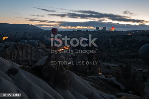 Many hot air balloons in dark early morning before rising in sky. Mountain landscape in Cappadocia. Colorful illuminated air balloons among volcanic rocks. Travel Goreme Turkey, 11 15 2018