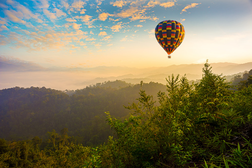 Colorful hot-air balloons flying over the mountain,Doi Inthanon National park in the sunrise and main road at Chiang Mai Province, Thailand