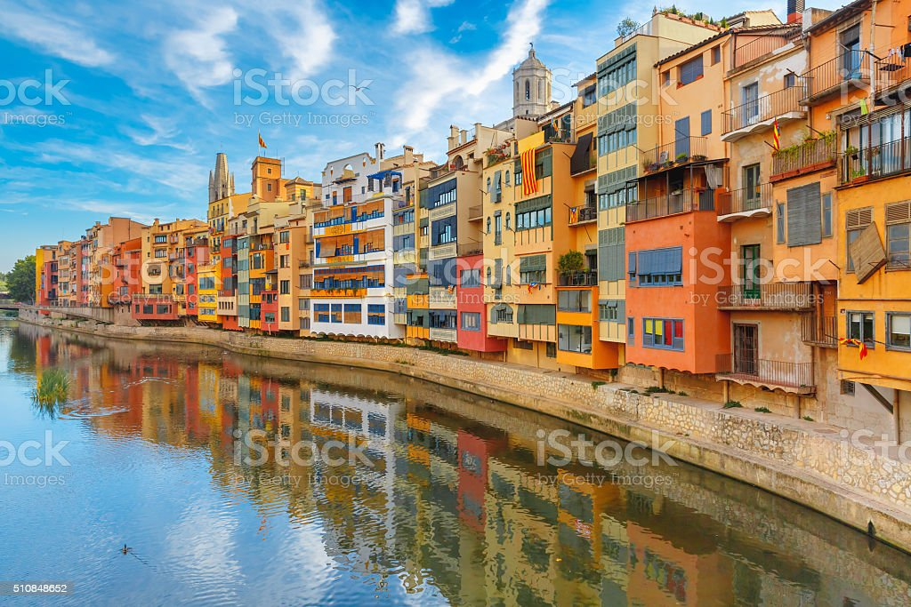 Colorful houses in Girona, Catalonia, Spain Colorful yellow and orange houses and famous house Casa Maso reflected in water river Onyar, in Girona, Catalonia, Spain. Church of Sant Feliu and Saint Mary Cathedral at background. Ancient Stock Photo