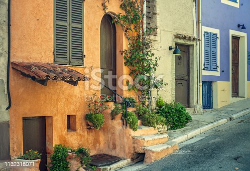 Row of colorful facades in a street of Cagnes-Sur-Mer, France. Some colors and details were digitally altered.