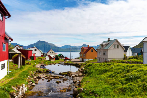 Colorful houses of Gjogv village and a small river flows into fjord. Faroe Islands, Denmark. stock photo