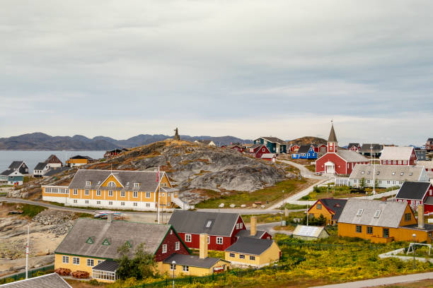 Colorful houses with the school Det gamle Sygehus, the cathedral and the statue of Hans Egede in the background, Nuuk. stock photo