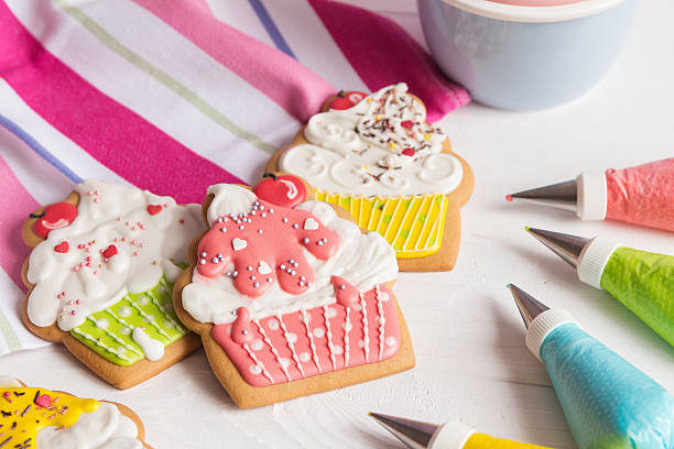 colorful icing cookies in cupcake shape - decorating stock photos and pictures