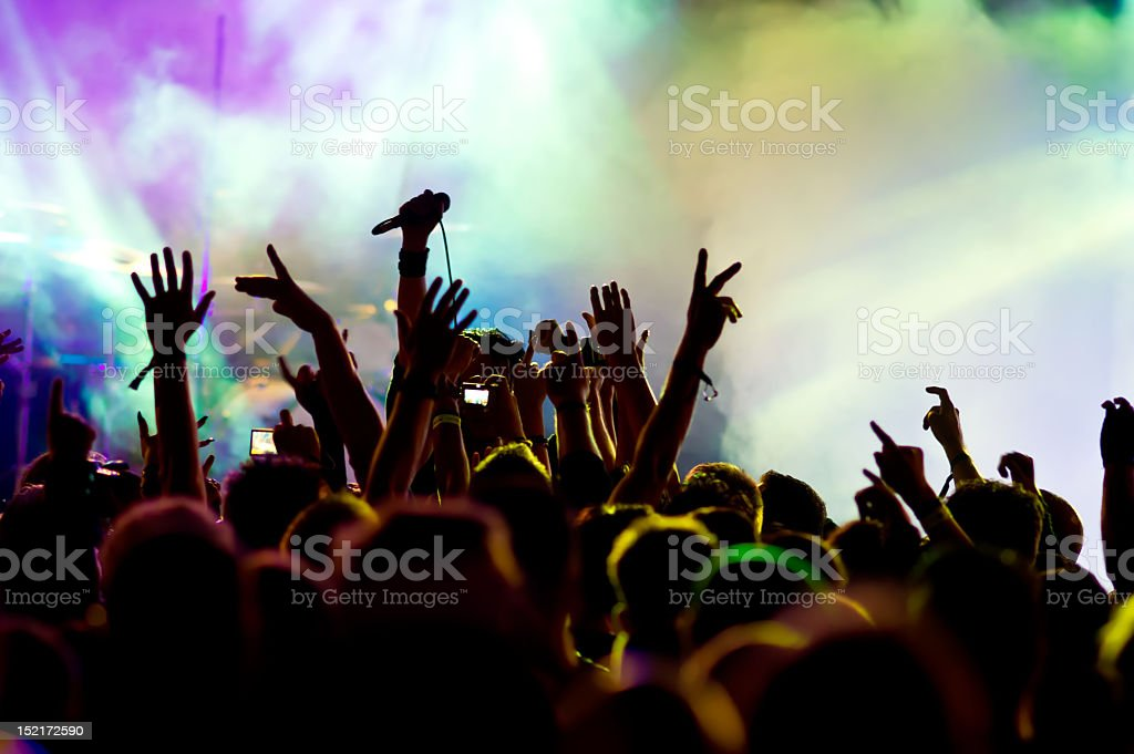 Colorful image of a smoke-filled concert setting & crowd stock photo