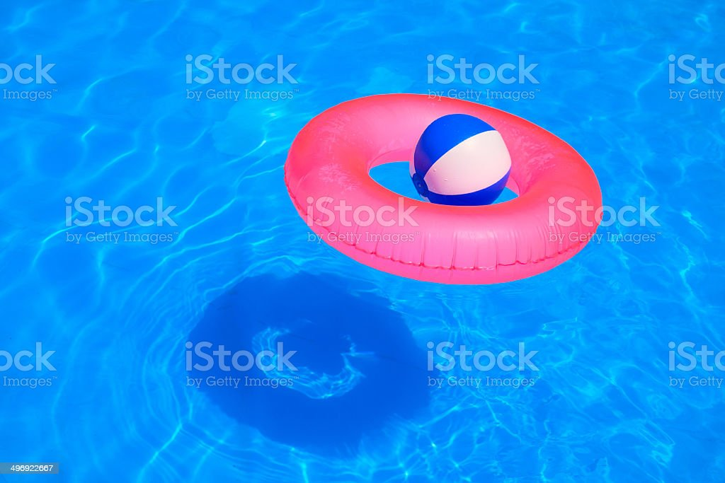 Colorful inflatable ball and round tube floating in swimming poo royalty-free stock photo