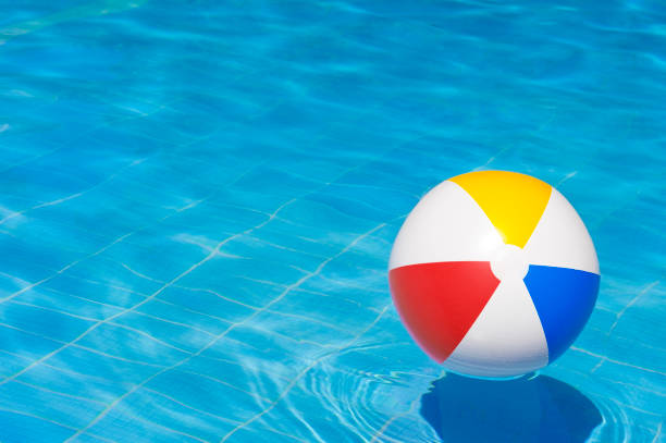 colorful inflatable ball floating in swimming pool, - brinquedos na piscina imagens e fotografias de stock