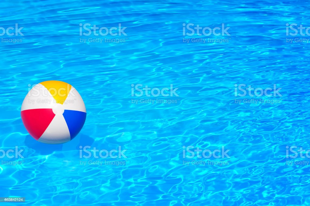 Colorful inflatable ball floating in swimming pool foto