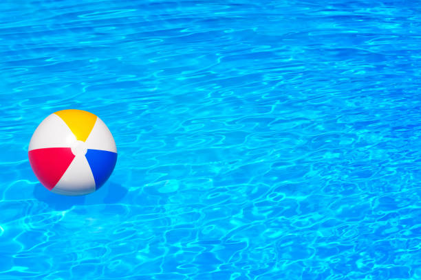 colorful inflatable ball floating in swimming pool - beach ball stock photos and pictures