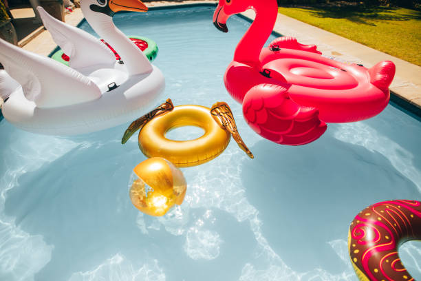 Colorful inflatable toys floating in a pool Group of colorful inflatable toys floating in a swimming pool on a summer day. Inflatable swan, flamingo, ring and ball in pool. swimming float stock pictures, royalty-free photos & images