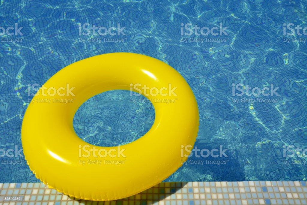 Colorful inflatable tube floating in swimming pool stock photo