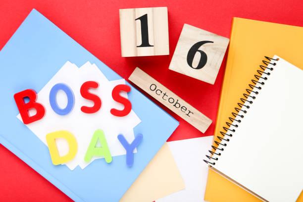 inscripción colorida boss day con calendario y blocs de notas sobre fondo rojo - boss's day fotografías e imágenes de stock