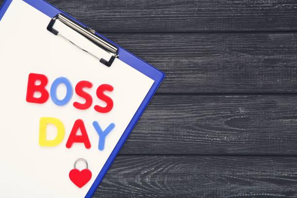 inscripción colorida boss day con portapapeles y candado en forma de corazón sobre fondo negro de madera - boss's day fotografías e imágenes de stock