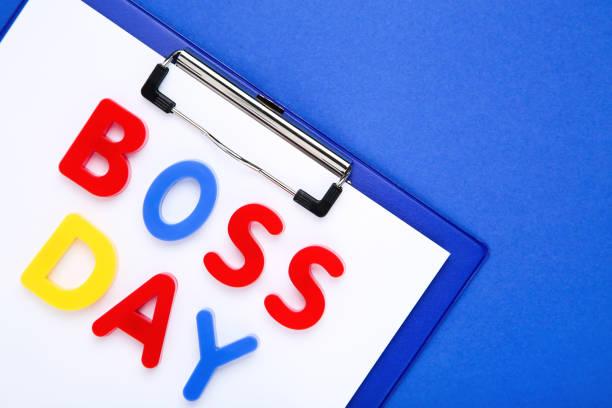 inscripción colorida boss day con portapapeles sobre fondo azul - boss's day fotografías e imágenes de stock