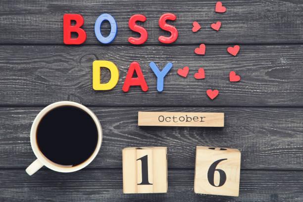 inscripción colorida boss day con taza de café y calendario sobre fondo de madera negra - boss's day fotografías e imágenes de stock