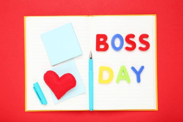 inscripción colorida boss day con corazón de tela, pluma, pegatinas y bloc de notas sobre fondo rojo - boss's day fotografías e imágenes de stock