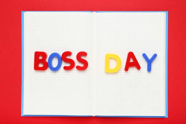 inscripción colorida boss day con bloc de notas sobre fondo rojo - boss's day fotografías e imágenes de stock