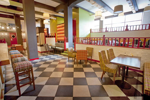 Ornamental chairs and tables located in stylish cafeteria with colorful walls and modern lamps