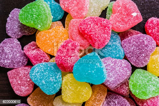 Colorful jelly cube candies on wooden floor