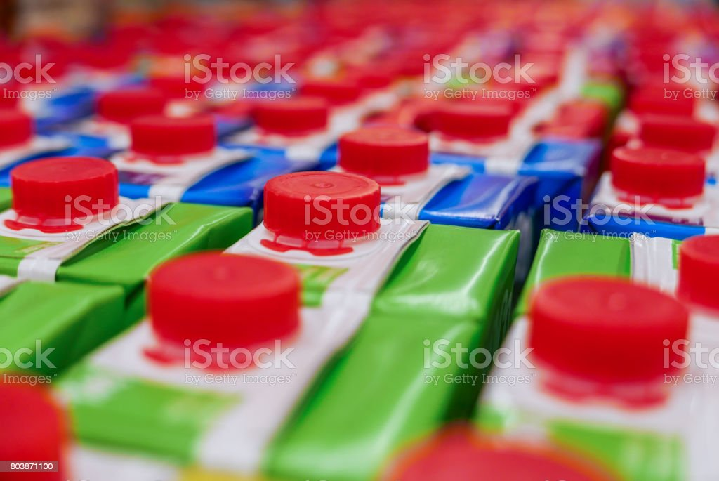 colorful Juice cartons with red screw cap in supermarket shelf. stock photo