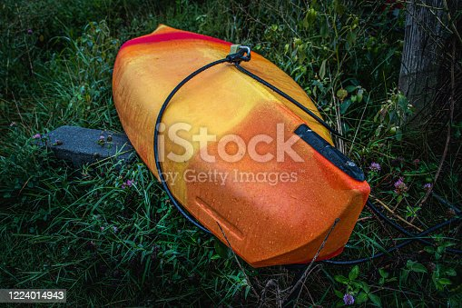 An orange and tellow kayak rests in a meadow next to Speedwell Forge Lake
