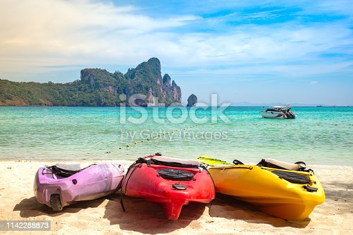 Colorful Kayaks On The Sand. Tropical beach with motor speed boat and cliffs on background. Summer active leisure.
