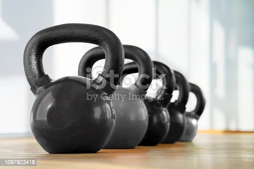Black kettlebells in a row in a gym