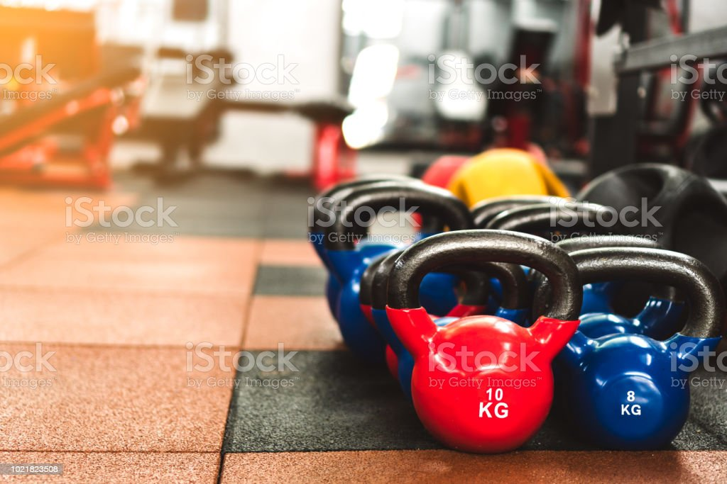 Colorful kettlebells on rubber floor in gym with sunlight effect for...