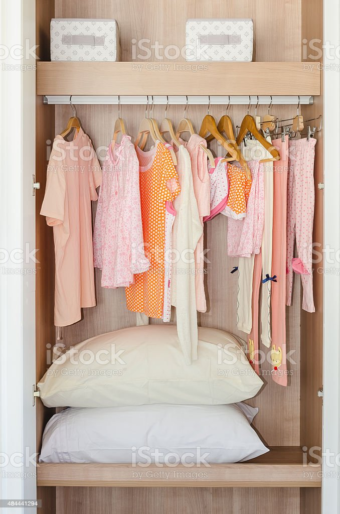 73c3e9e90 Colorful Kids Clothes Hanging On Bar In Wooden Wardrobe Stock Photo ...