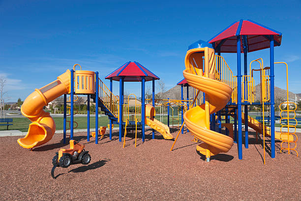 Colorful kids outdoor playground equipment with slides Colorful Playground In A Park During Early Summer leisure equipment stock pictures, royalty-free photos & images