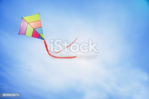 angle view of a colorful kite flying with waving red bow in a deep blue sky with the light of the sun