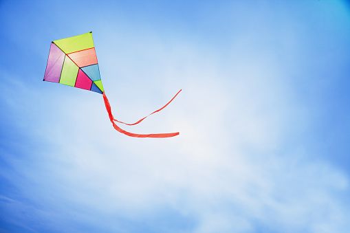 colorful kite flying with waving red bow