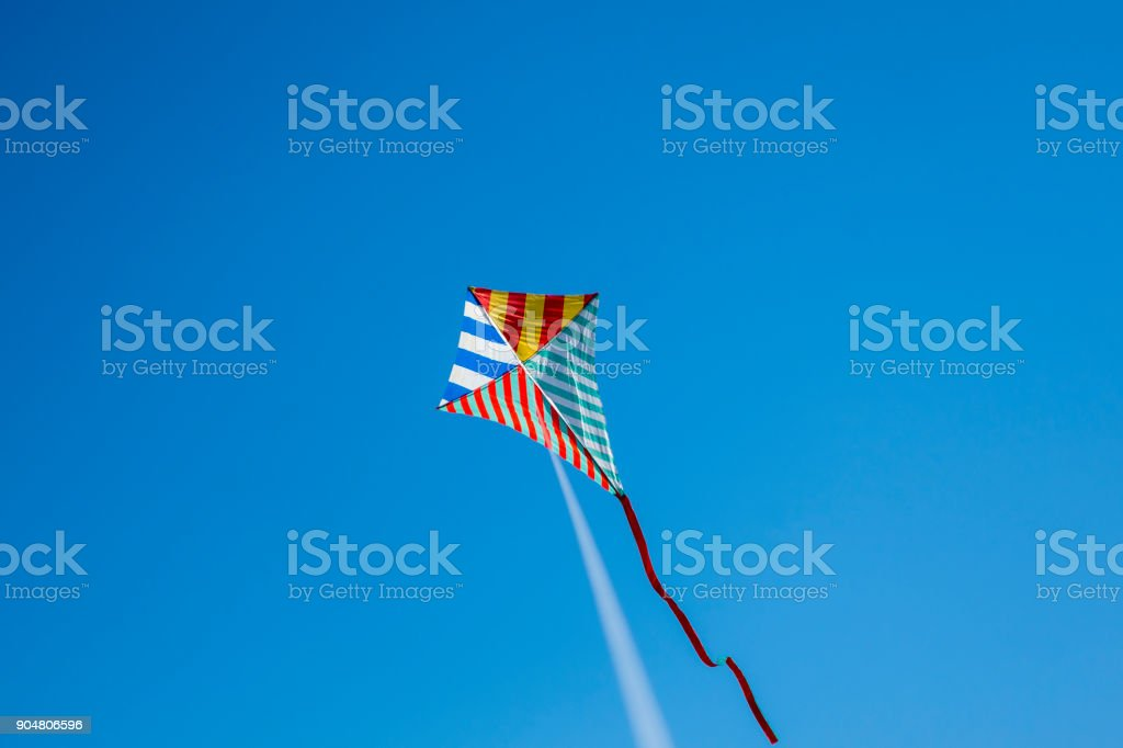 Colorful kite flying with waving red bow - foto stock