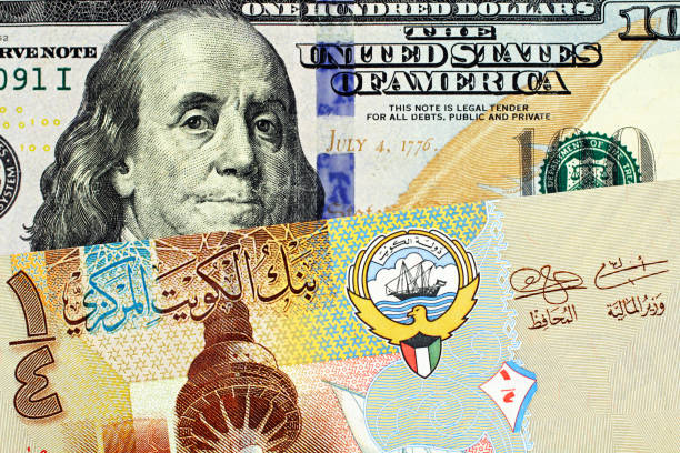 a colorful kuwaiti quarter dinar with an american one hundred dollar bill close up - kuwait currency stock photos and pictures